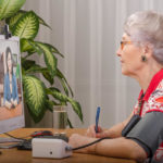 Old grey haired woman is measuring blood pressure by herself during virtual doctor visit. Glasses senior woman sitting opposite monitor. On the screen, telehealth doc is consulting her. Side shot